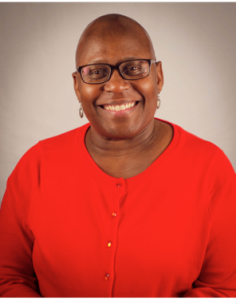 Image Description: An African American woman stands against a grey background. She is smiling at the camera, she is bald has glasses, and is wearing a red button up shirt
